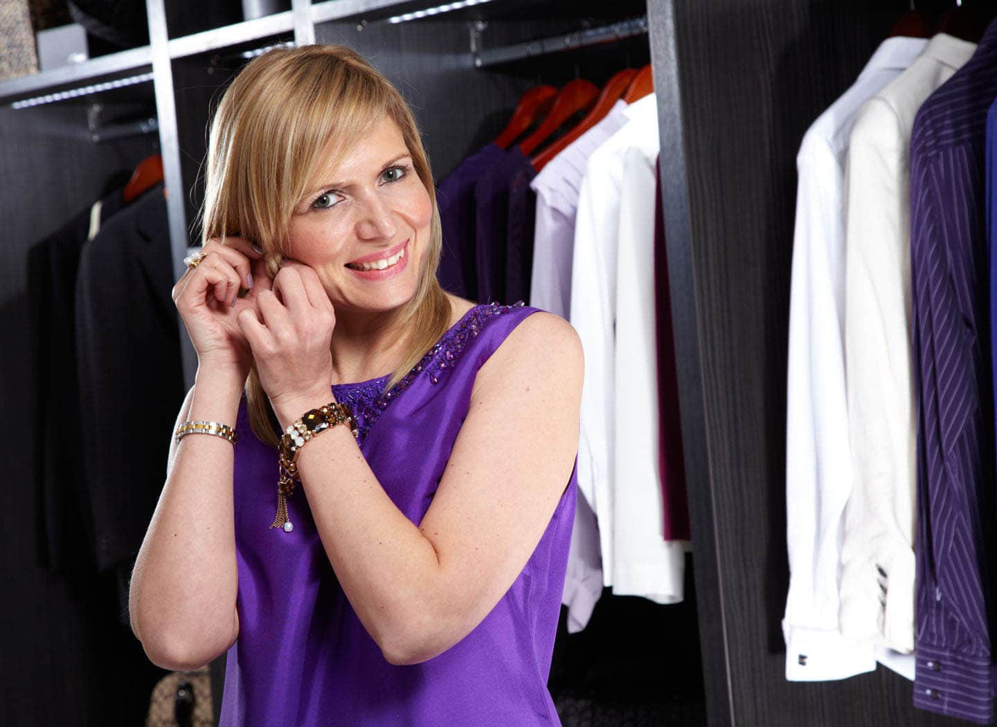 Woman putting jewellery on in made to measure dressing room