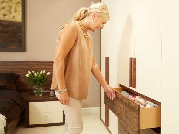Woman opening bespoke drawers in Walnut