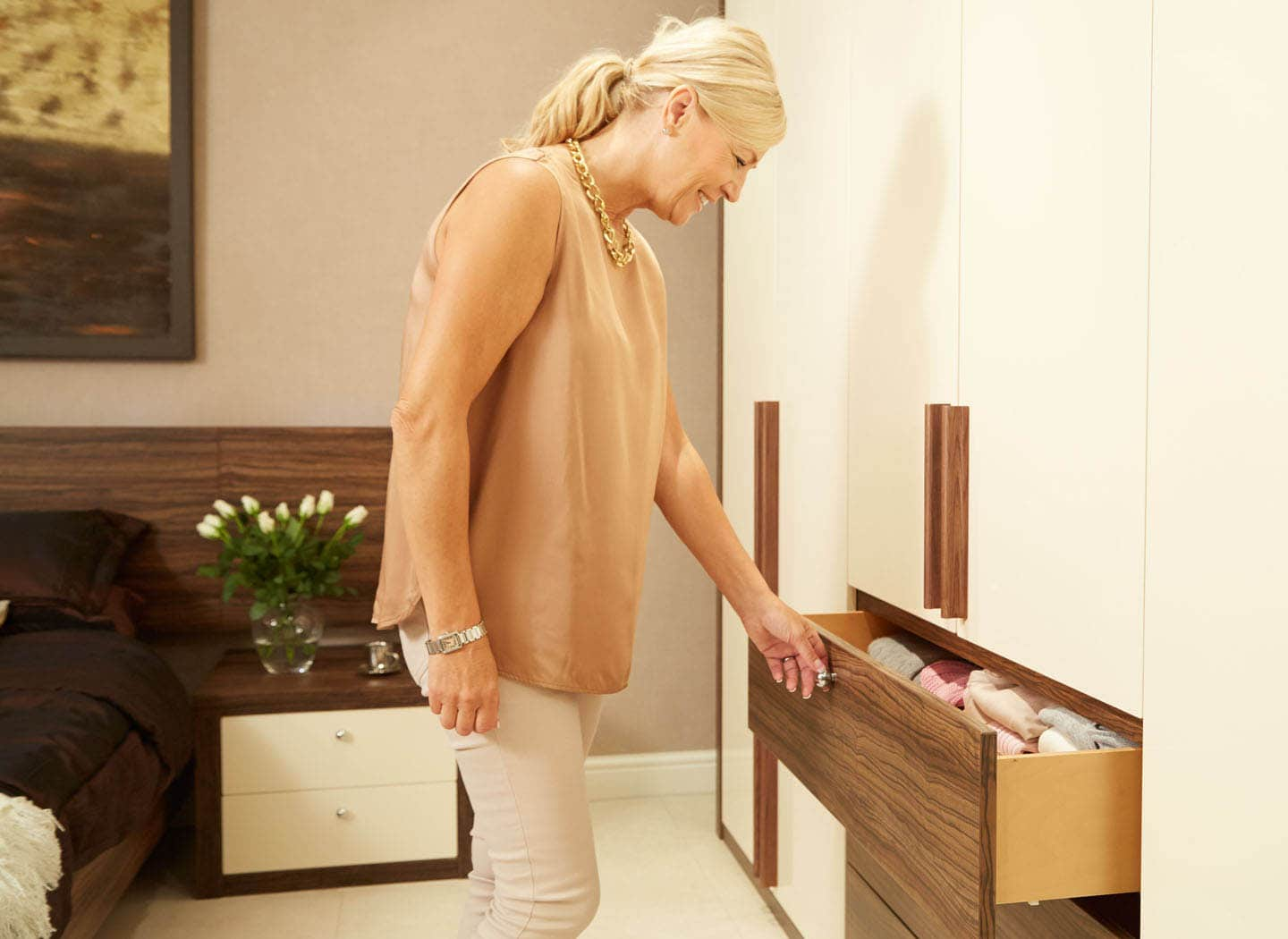 Woman opening bespoke drawers in Walnut