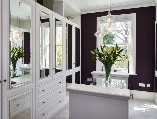 A traditional dove white dressing room with luxurious detail & mirrored wardrobe doors