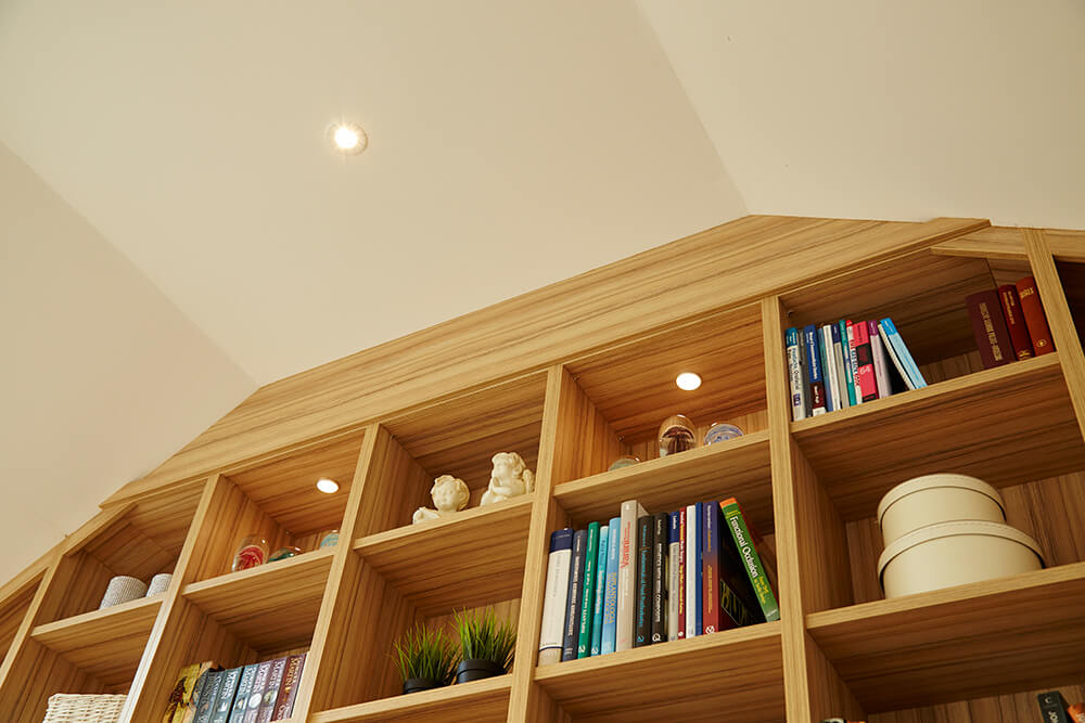 Shaped bookcase units designed to fit angles of ceiling