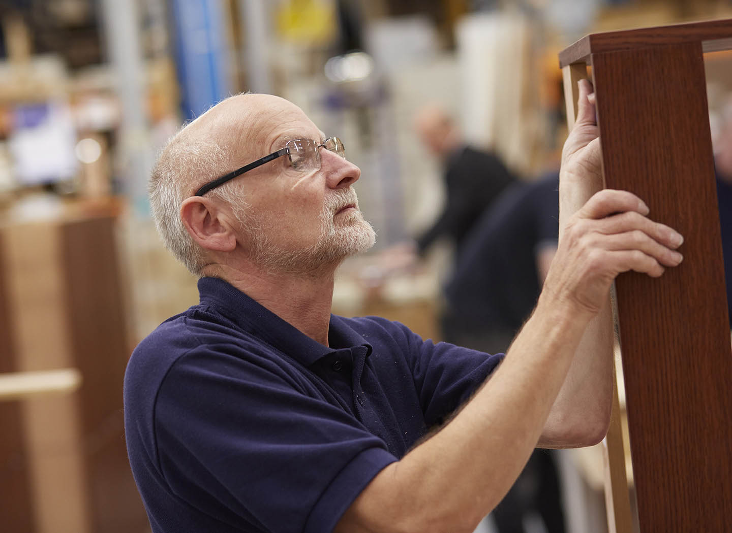 One of our craftsmen inspecting furniture in our Strachan Leeds workshop