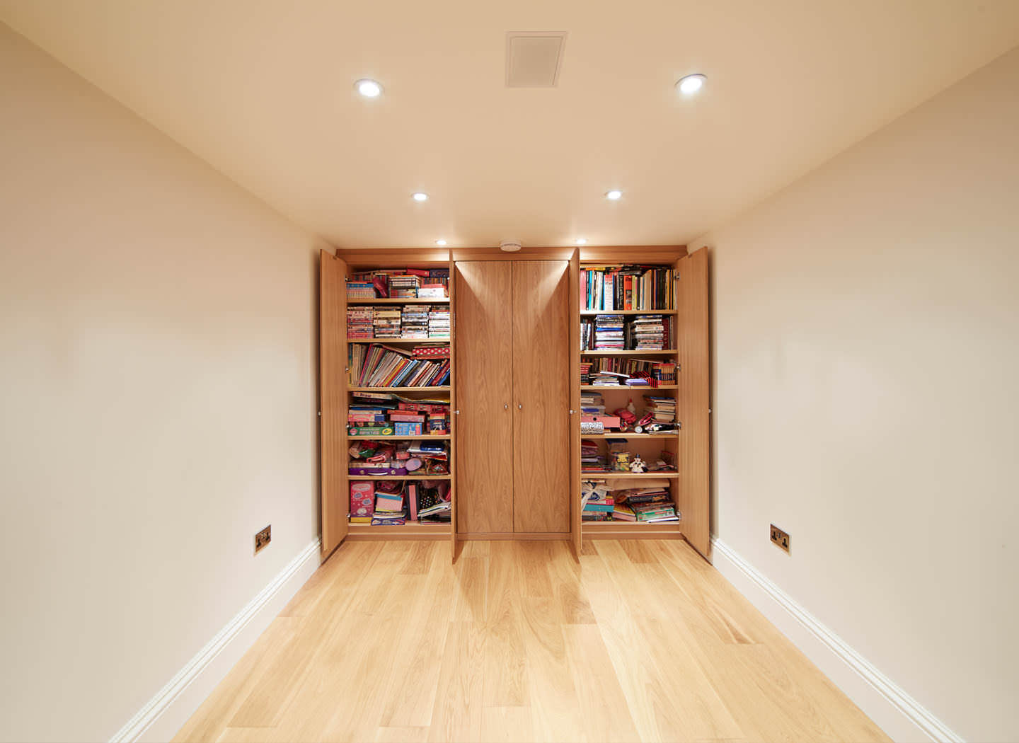 Case study showing fitted cupboard and bookshelves in basement conversion