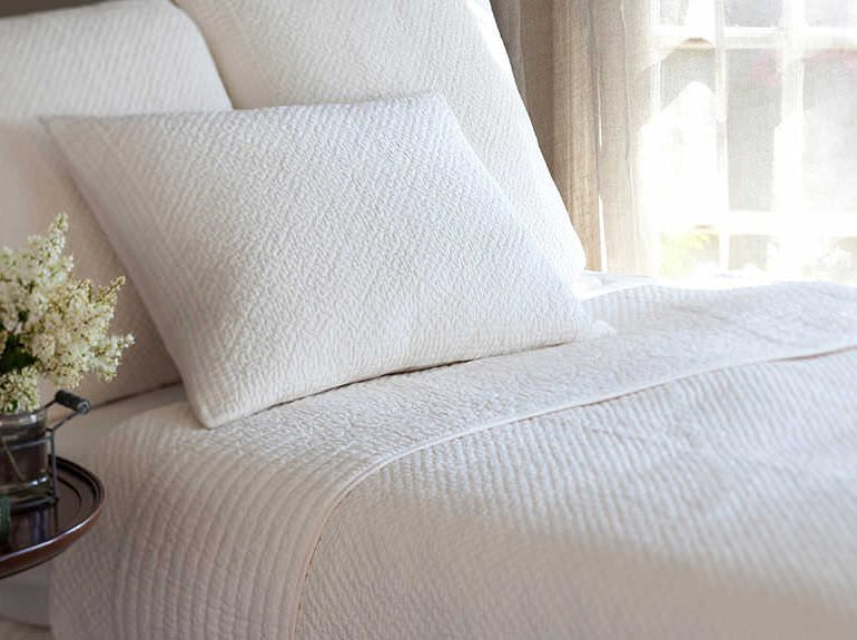 Bed linen and throw in neutral colour scheme