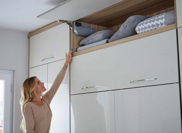 Woman activating the smart sensor to close the overhead cupboard