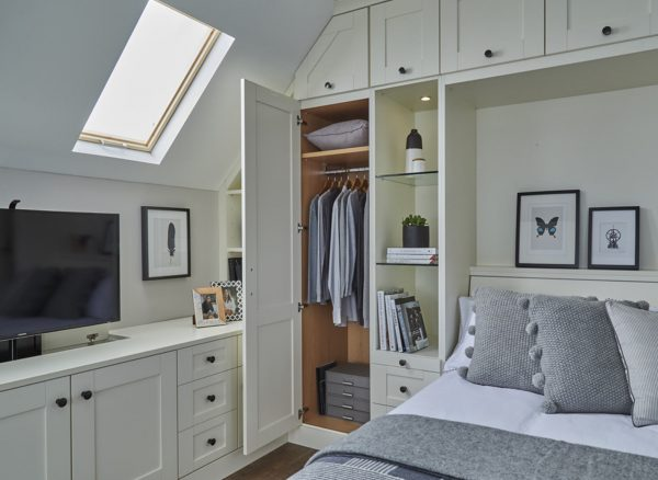 Classic, white fitted bedroom with wall bed and open wardrobe showing interior storage