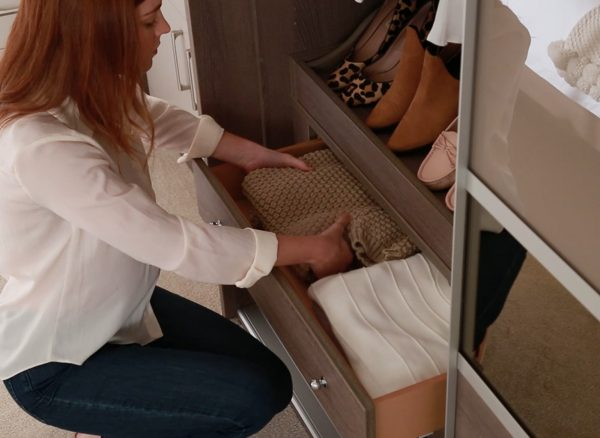 Woman pulling clothes from her fitted wardrobe drawers
