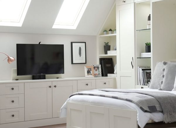 Fitted bedroom furniture with pop-up television storage solution