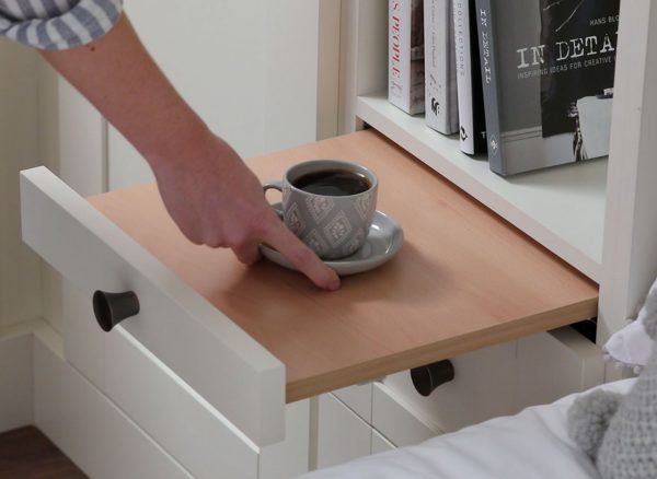 Woman putting down a cup of coffee on a pull out bedside table