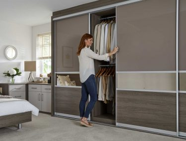 Woman sliding open the door of a floor to ceiling fitted wardrobe