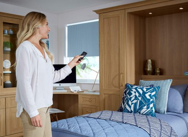 Woman using a remote to activate the Oak wall bed integrated LED lighting system