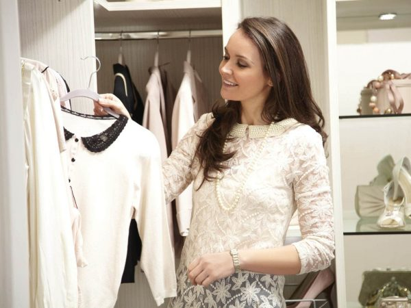 Woman putting away clothes in white walk in wardrobe